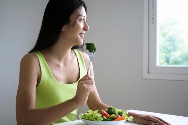 Een gelukkige aziatische vrouw met een gezonde saladeschotel, die vork met grote broccoli houdt. eten voor een goede vorm