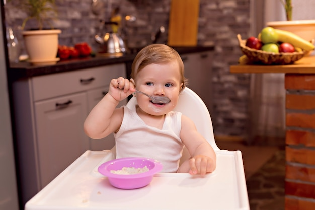 Een gelukkige baby van 10-12 maanden eet melkpap met een lepel. portret van een gelukkig meisje in een kinderstoel in de keuken