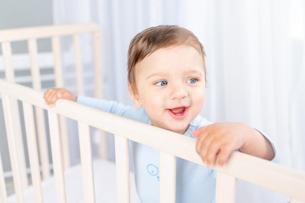 Een gelukkige babyjongen in een wieg in de kinderkamer houdt zich aan de zijkant vast en lacht