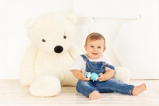 Een gelukkige babyjongen van zes maanden oud in een gebreid warm jasje en een blauwe spijkerbroek kruipt thuis in de buurt van een grote teddybeer