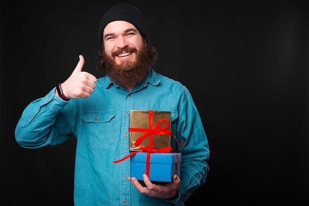 Een gelukkige bebaarde man glimlacht naar de camera en houdt een duim omhoog en een aantal cadeautjes laat zien dat hij de cadeautjes leuk vindt