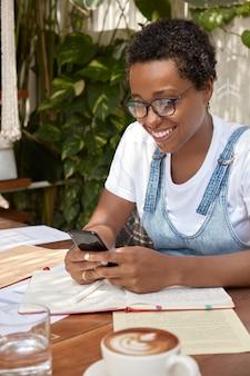 Een gelukkige beheerder zit op het bureaublad, communiceert met collega's in sociale netwerken, deelt ervaringen