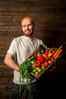 Een gelukkige boer in een witte t-shirt en hoed houdt een mand met verse groenten en fruit