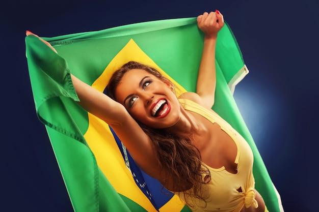 Een gelukkige braziliaanse fan juicht met vlag