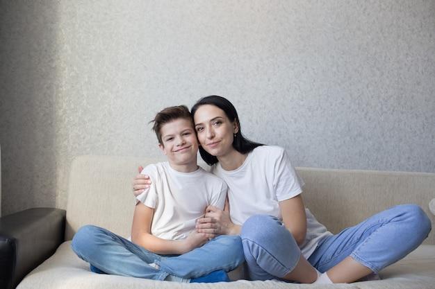 Een gelukkige brunette moeder in een witte t-shirt en spijkerbroek knuffelt haar liefdevolle zoon om thuis op de bank te zitten