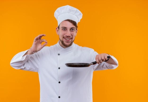 Een gelukkige chef-kokmens in wit uniform die koekenpan houdt terwijl hij smakelijk ok gebaar op een oranje muur toont