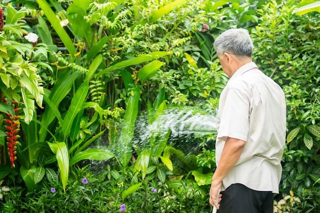 Een gelukkige en glimlachende aziatische oude bejaarde man geeft planten en bloemen water voor een hobby na pensionering in een huis