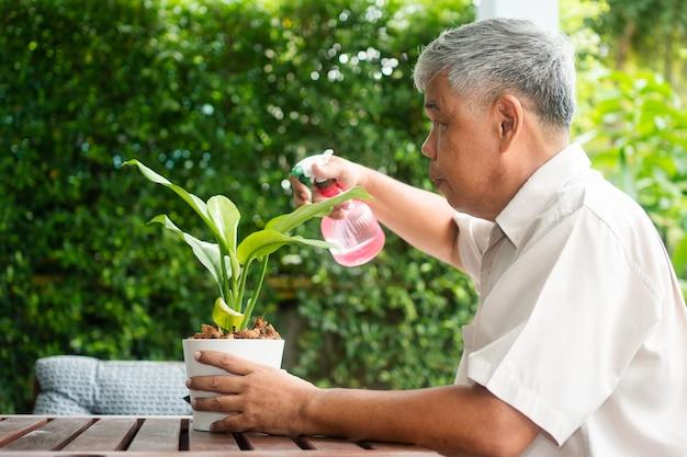 Een gelukkige en glimlachende aziatische oude bejaarde man plant voor een hobby na zijn pensionering in een huis. concept van een gelukkige levensstijl en een goede gezondheid voor senioren.
