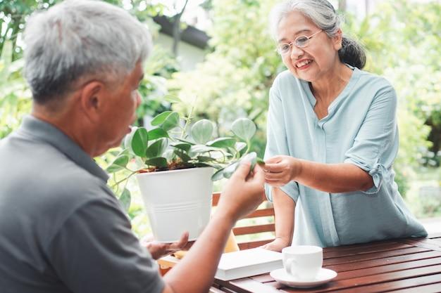 Een gelukkige en glimlachende aziatische oude bejaarde vrouw plant voor een hobby na pensionering met haar echtgenoot.