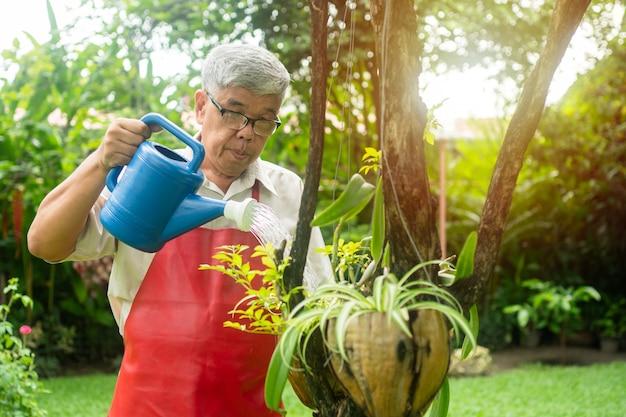 Een gelukkige en glimlachende aziatische oude oudere man geeft na zijn pensionering planten en bloemen water voor een hobby