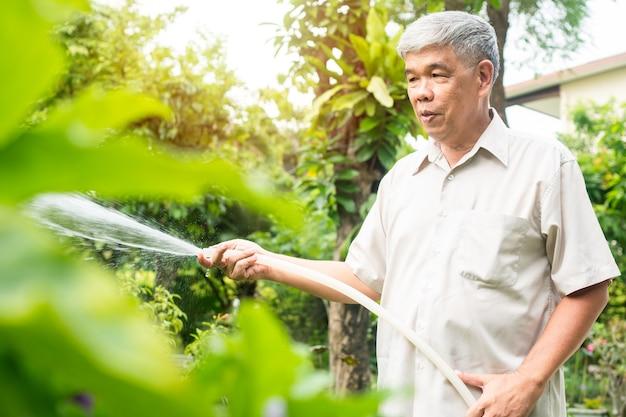 Een gelukkige en glimlachende aziatische oude oudere man geeft planten en bloemen water voor een hobby na zijn pensionering