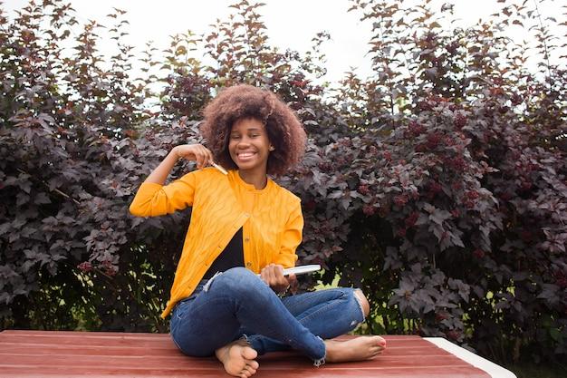 Een gelukkige en jonge afrikaanse amerikaanse student in het park