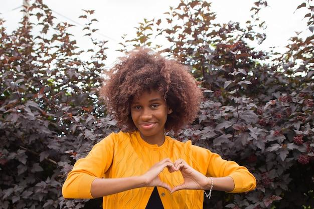 Een gelukkige en jonge awoman toont een hart met haar handen