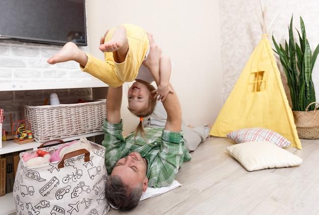 Een gelukkige en liefdevolle vader speelt thuis met zijn dochtertje