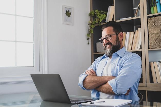 Een gelukkige en tevreden man lacht en kijkt naar zijn werk op het computerscherm. mannelijke mensen ontspannen na het beëindigen van het werk in het kantoor van thuis binnenshuis.