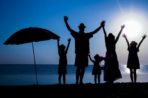 Een gelukkige familie aan zee bij zonsondergang in reissilhouet in de natuur