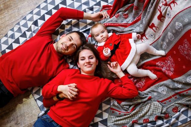 Een gelukkige familie in rode truien zit samen op de vloer. kerst vakantie sfeer. een kind in een kerstmankostuum. familie relatie concept