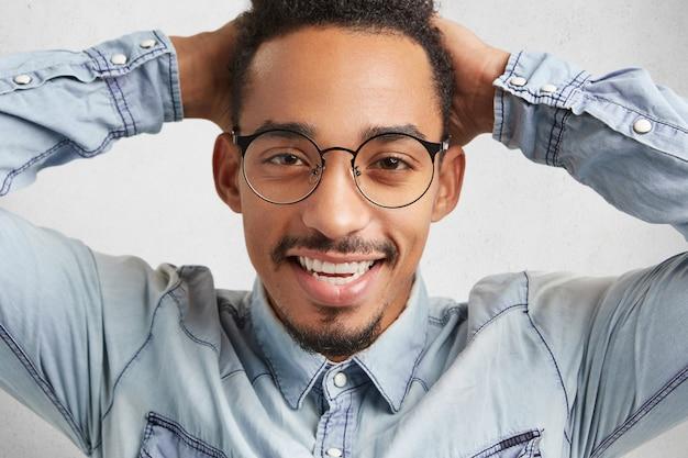 Een gelukkige hipster met een grote ronde bril voelt zich ontspannen
