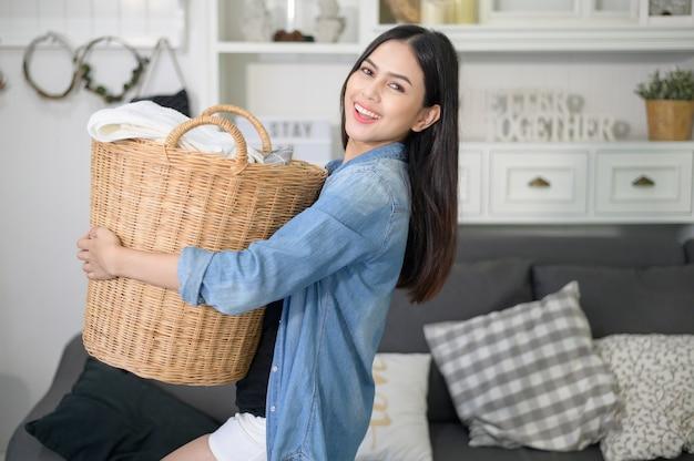 Een gelukkige huishoudster draagt een emmer met wasgoed in huis.