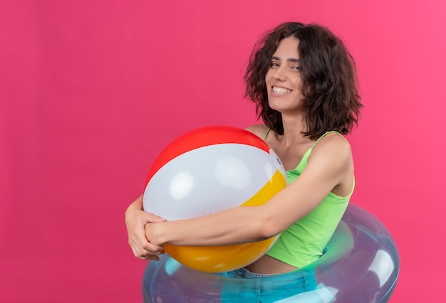 Een gelukkige jonge aantrekkelijke vrouw met kort haar in een groene crop top glimlachend en met opblaasbare bal