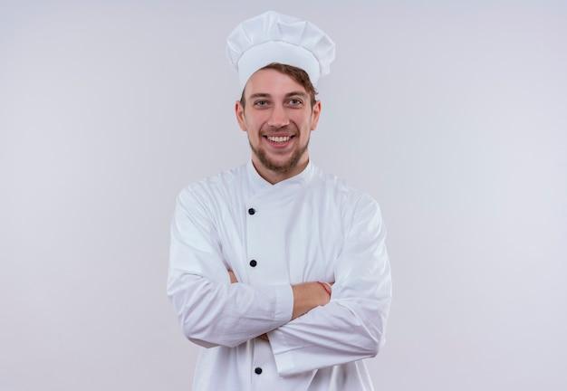 Een gelukkige jonge bebaarde chef-kok man met een wit fornuis uniform en hoed glimlachend en hand in hand gevouwen terwijl het kijken op een witte muur