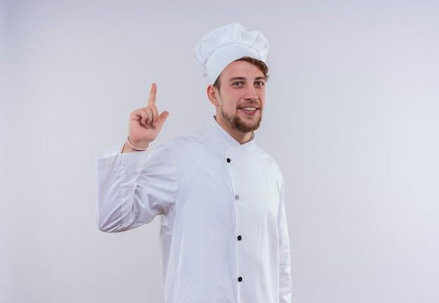 Een gelukkige jonge, bebaarde chef-kokmens die een wit fornuisuniform draagt en een hoed die omhoog wijst terwijl hij op een witte muur kijkt