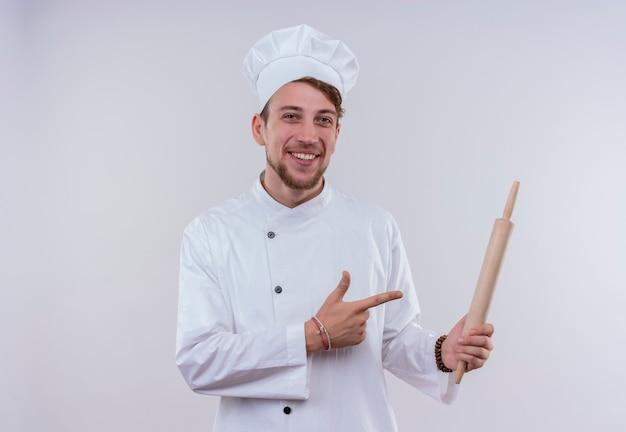 Een gelukkige jonge, bebaarde chef-kokmens die een wit fornuisuniform draagt en een hoed die op deegroller richt terwijl hij op een witte muur kijkt