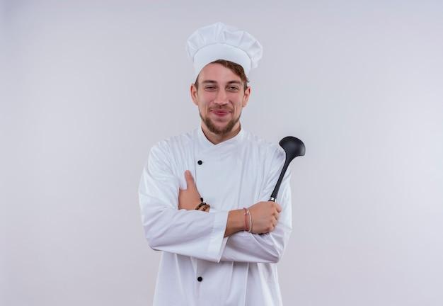 Een gelukkige jonge, bebaarde chef-kokmens die een wit fornuisuniform draagt en een hoed die zwarte pollepel houdt terwijl hij op een witte muur kijkt