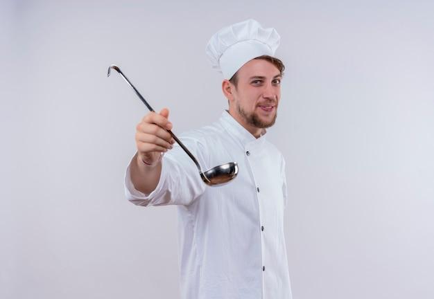 Een gelukkige jonge, bebaarde chef-kokmens die wit eenvormig fornuis en hoed draagt ?? die pollepel toont terwijl hij op een witte muur kijkt
