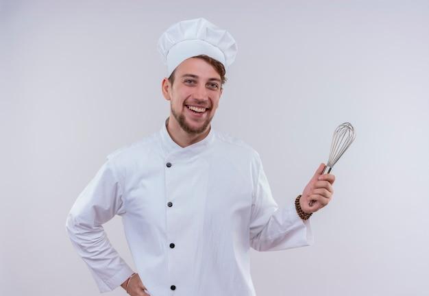 Een gelukkige jonge, bebaarde chef-kokmens die wit fornuisuniform draagt en hoed glimlacht en mixerlepel vasthoudt terwijl hij op een witte muur kijkt
