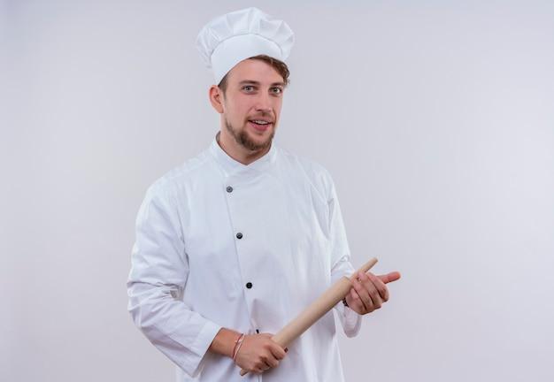 Een gelukkige jonge, bebaarde chef-kokmens die wit fornuisuniform draagt en hoed houdt deegroller terwijl hij op een witte muur kijkt