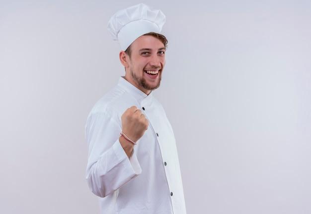 Een gelukkige jonge, bebaarde chef-kokmens die wit fornuisuniform en hoed draagt, glimlacht en gebalde vuist toont terwijl hij op een witte muur kijkt