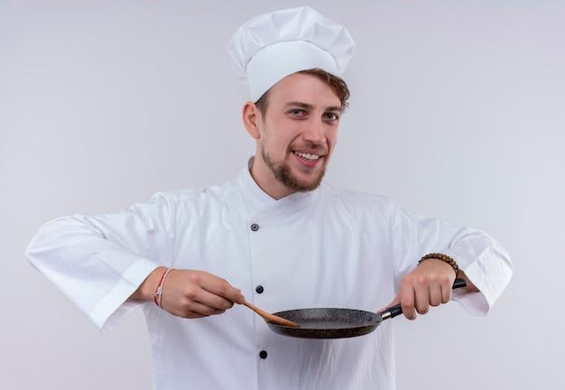 Een gelukkige jonge, bebaarde chef-kokmens die witte uniforme fornuis en hoed draagt die houten lepel op koekenpan houdt terwijl hij op een witte muur kijkt