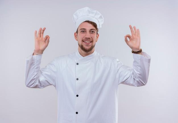 Een gelukkige jonge bebaarde chef-kokmens in wit uniform die ok gebaar met twee handen op een witte muur toont