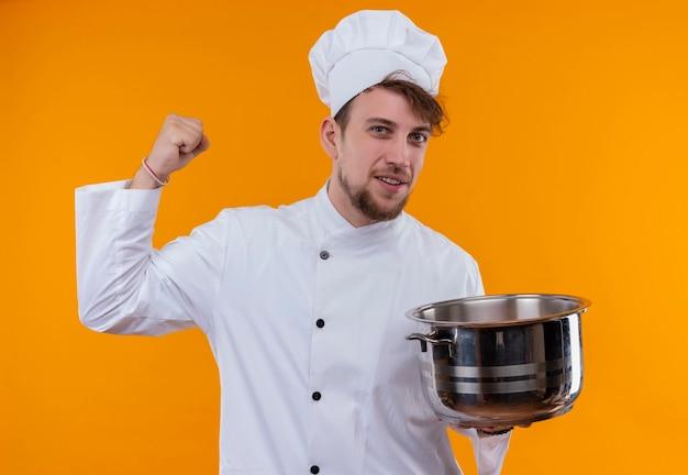 Een gelukkige jonge, bebaarde chef-kokmens in wit uniform die sauspan houdt en gebalde vuist toont terwijl hij op een oranje muur kijkt