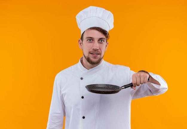 Een gelukkige jonge bebaarde chef-kokmens in wit uniform die zwarte koekenpan houdt terwijl hij op een oranje muur kijkt