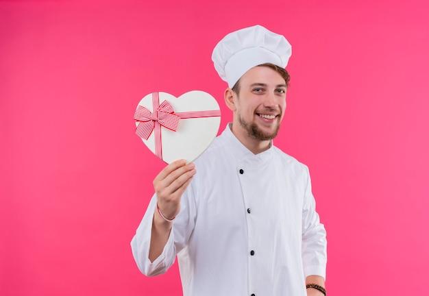 Een gelukkige jonge bebaarde chef-kokmens in wit uniform glimlacht en toont hartvormige giftdoos op een roze muur