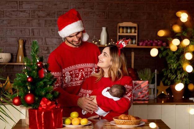 Een gelukkige jonge familie moeder vader en baby in rode truien in de keuken met een kerstboom thuis vieren nieuwjaar of kerstmis vreugde in het geschenk van de geboorte van een kind