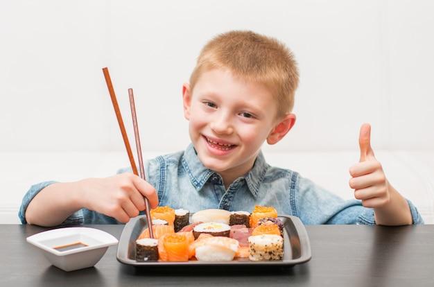 Een gelukkige jonge jongen klaar om sushi te eten