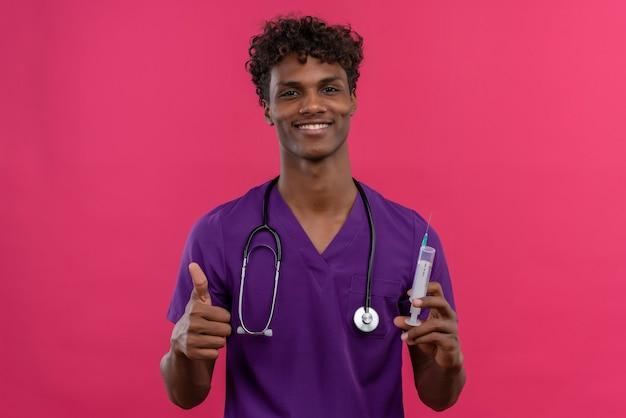 Een gelukkige jonge knappe dokter met een donkere huid en krullend haar in violet uniform met een stethoscoop die duimen toont terwijl hij een injectiespuit vasthoudt