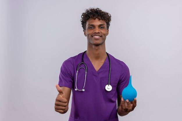 Een gelukkige jonge knappe dokter met een donkere huid en krullend haar in violet uniform met een stethoscoop die duimen toont terwijl hij een klysma vasthoudt