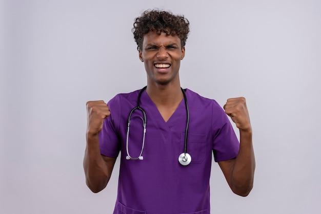 Een gelukkige jonge knappe donkere arts met krullend haar die violet uniform met een stethoscoop draagt die gebalde vuist houdt