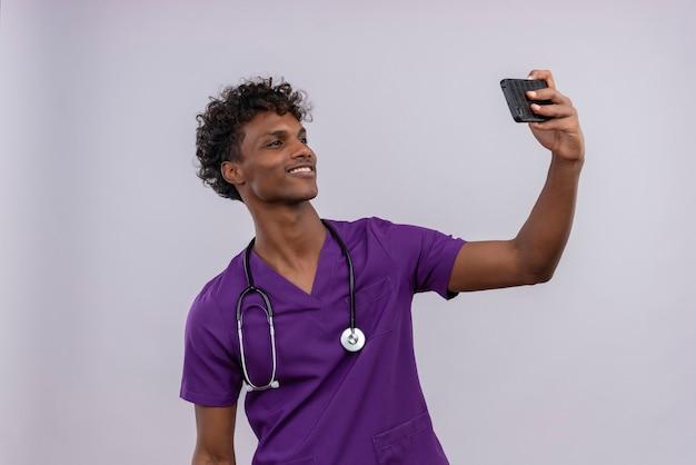 Een gelukkige jonge knappe donkere arts met krullend haar die violet uniform met een stethoscoop dragen die selfie met mobiele telefoon neemt