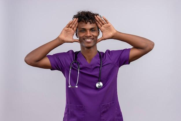 Een gelukkige jonge knappe donkere arts met krullend haar draagt violet uniform met een stethoscoop hand in hand op het hoofd