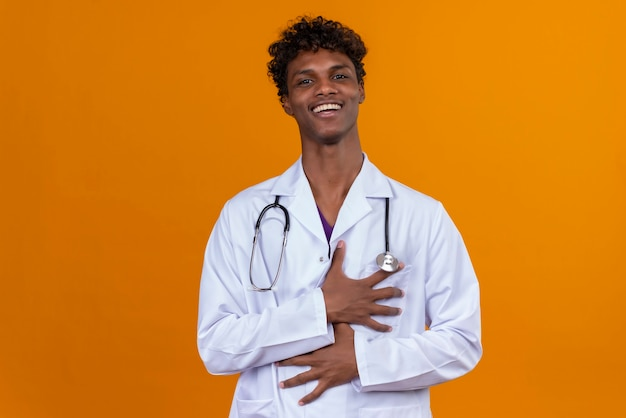Een gelukkige jonge knappe donkere man met krullend haar, gekleed in een witte jas met een stethoscoop glimlachend en hand in hand