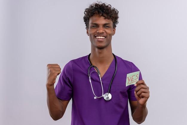 Een gelukkige jonge knappe donkere mannelijke arts met krullend haar draagt violet uniform met een stethoscoop met een papieren kaart met het woord ja