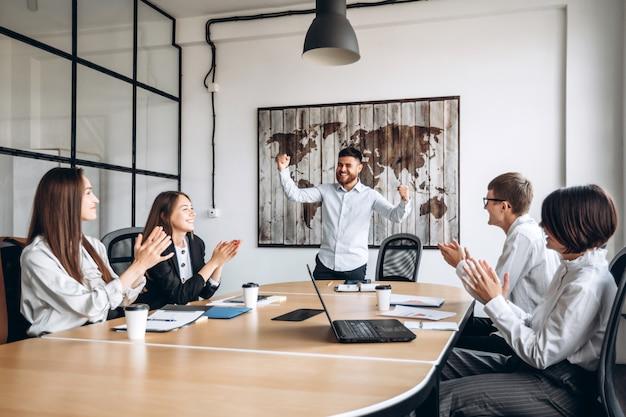 Een gelukkige jonge knappe man bebaarde man maakt winnaar gebaar in kantoor. verheugt zich met zijn collega's