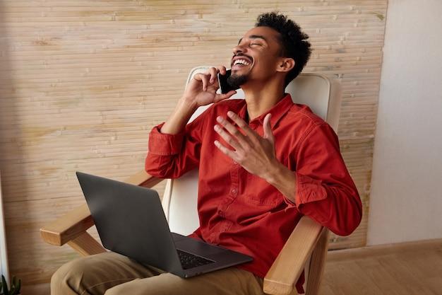 Een gelukkige jonge kortharige, bebaarde, donkere man die zijn hoofd achterover buigt terwijl hij lacht en emotioneel zijn hand opheft, telefoneert terwijl hij in een stoel zit