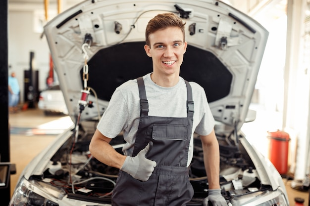 Een gelukkige jonge man is aan het werk. autoservice en onderhoud.