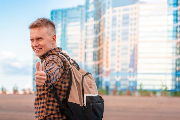 Een gelukkige jonge man steekt zijn duim op